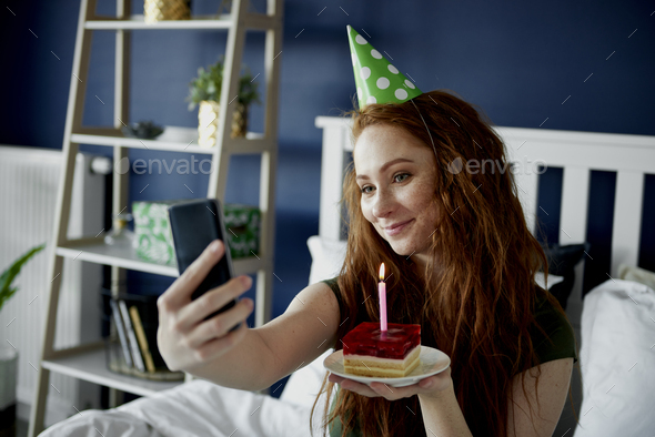 Woman taking a selfie with birthday cake - Stock Photo - Images