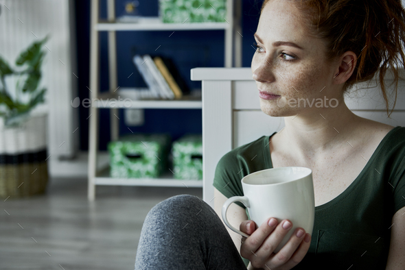 Nostalgic young woman and a cup of tea - Stock Photo - Images