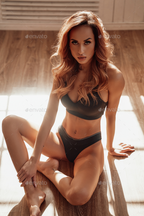 Sexy and fit woman sitting in lotus pose on the wooden floor wearing black sportive lingerie - Stock Photo - Images