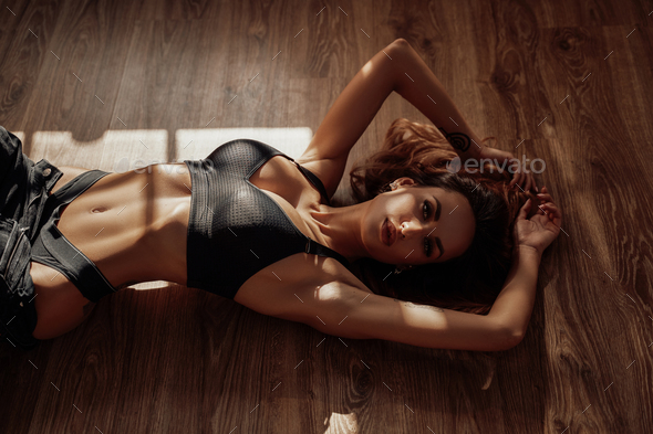 Young and beautiful semi-naked woman in sporty black lingerie laying on the floor in apartment - Stock Photo - Images