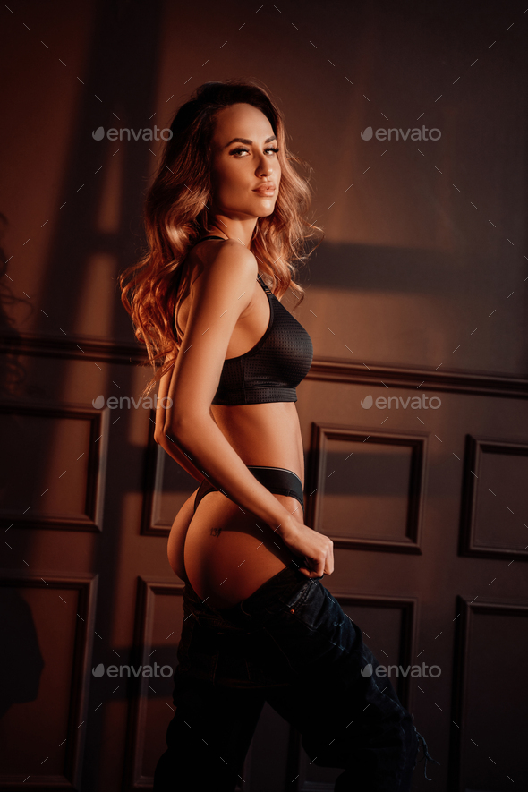 Gorgeous woman showing her body wearing sportive black lingerie in a dark apartment - Stock Photo - Images