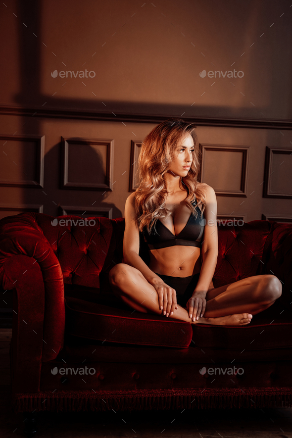 Gorgeous woman sitting on a sofa, wearing sportive black lingerie in a dark apartment - Stock Photo - Images