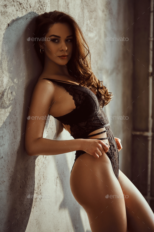 Young female model with dark hair and lace underwear posing in a bright room - Stock Photo - Images