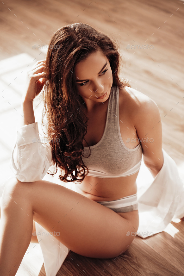 Beautiful female model relaxing on a wooden floor in a luxury apartment wearing sporty underwear - Stock Photo - Images