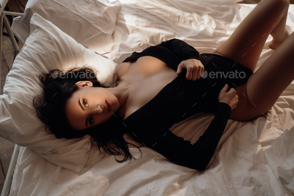 Goregeous woman showing her body wearing body costume among bed sheets - Stock Photo - Images