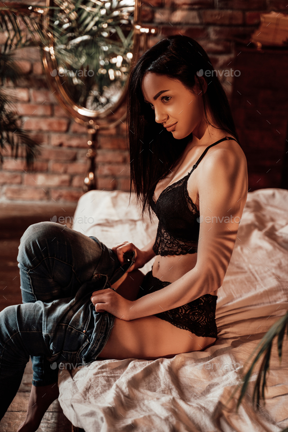 Lovely and smooth young lady sitting on the bed in a luxury flat wearing sexy lingerie - Stock Photo - Images