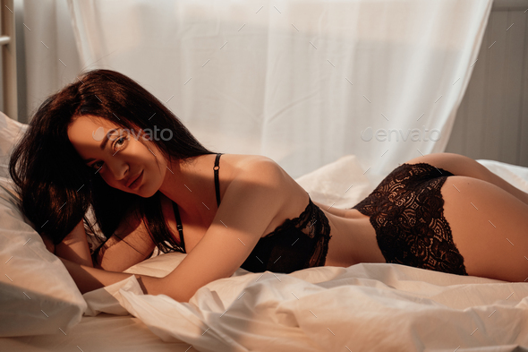 Graceful woman with dark hair wearing black lace lingerie laying on a bed among white sheets - Stock Photo - Images