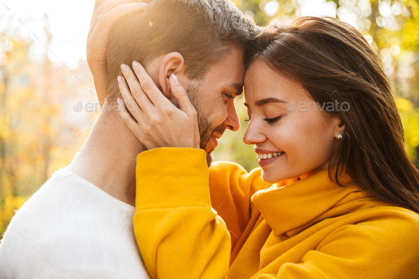 Beautiful young happy couple in love embracing - Stock Photo - Images