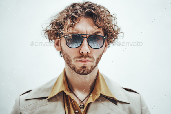 Portrait of a young man with curly hair posing in a bright studio looking vogue - Stock Photo - Images