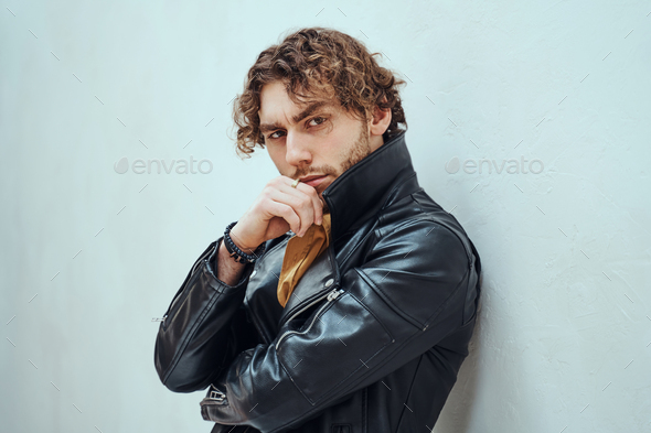 Daring and cool man with curly hair posing in leather coat in a bright studio - Stock Photo - Images
