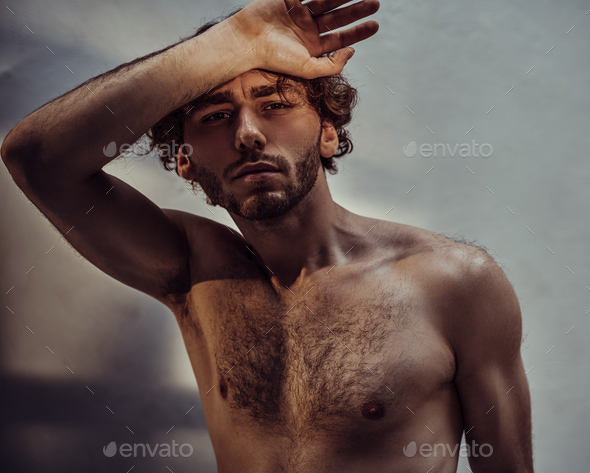 Young caucasian male model is naked and isolated on the grey background - Stock Photo - Images