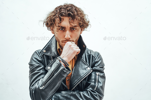 Young and and thoughtful male model with curly hair posing in a studio wearing leather jacket - Stock Photo - Images