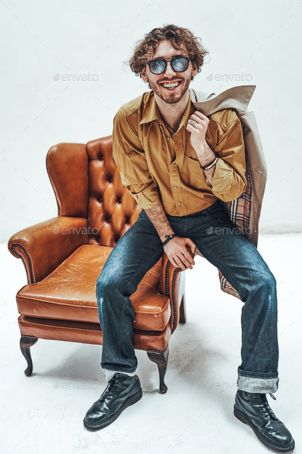 Handsome casual guy with curly hair posing in the bright studio while sitting on leather chair - Stock Photo - Images