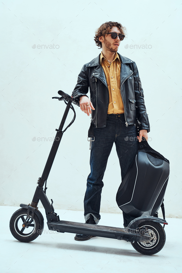 Assertive and rich young man posing on a scooter in a bright studio, looking cool - Stock Photo - Images
