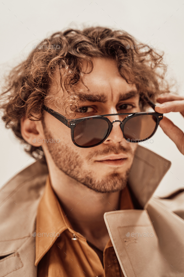 Portrait of a handsome casual guy with curly hair posing in the bright studio - Stock Photo - Images