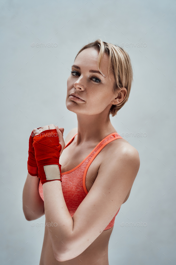 Sportive adult female model with blonde hair and orange fitness bra posing in a bright room - Stock Photo - Images