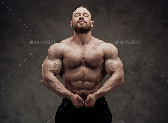 Athletic man isolated on a grey background is showing his chest muscle - Stock Photo - Images