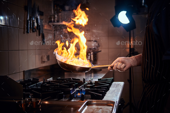 Cooker wearing gloves and apron frying flambe on a pan in a dark restaurant kitchen - Stock Photo - Images