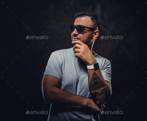 Adult handsome man in a grey shirt and sunglasses - Stock Photo - Images