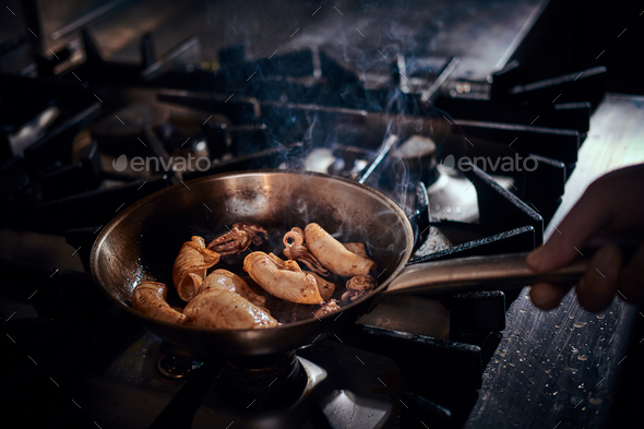 Chef cooking stir-fry seafood with squids and fish using a pan in a dark restaurant kitchen - Stock Photo - Images
