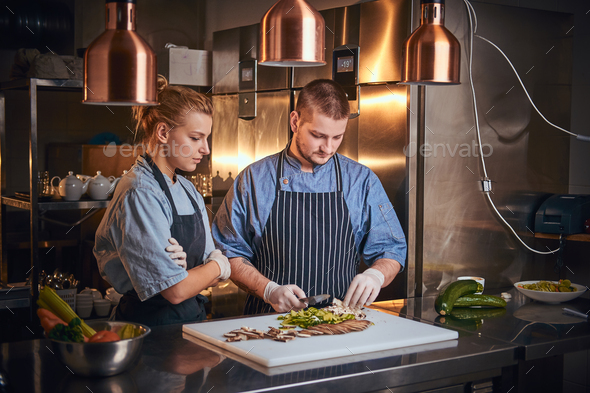 Male chef with assistant standing in a kitchen, preparing food in a luxury restaurant - Stock Photo - Images