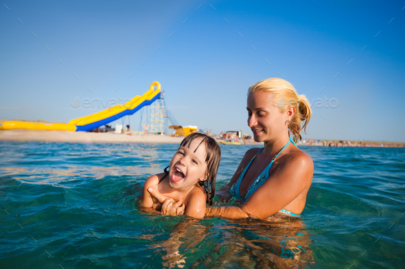 Young mother standing in water and helping to swim her small daughter - Stock Photo - Images