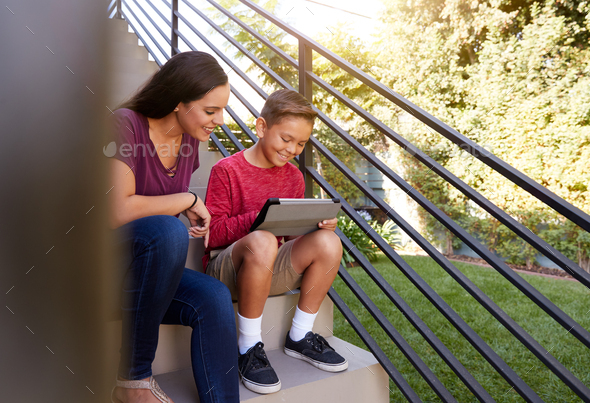 Mother Sitting On Steps Outdoors At Home With Son Using Digital Tablet - Stock Photo - Images