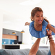 Father Playing Game With Daughter Lying On Sofa And Lifting Her In The Air - PhotoDune Item for Sale