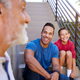 Smiling Multi-Generation Male Hispanic Family Sitting On Steps In Garden And Talking Together - PhotoDune Item for Sale