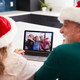 Multi-Generation Hispanic Family Wearing Santa Hats With Laptop Having Video Chat At Christmas - PhotoDune Item for Sale