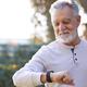 Senior Hispanic Man Checking Health Monitor On Smart Watch In Garden At Home - PhotoDune Item for Sale