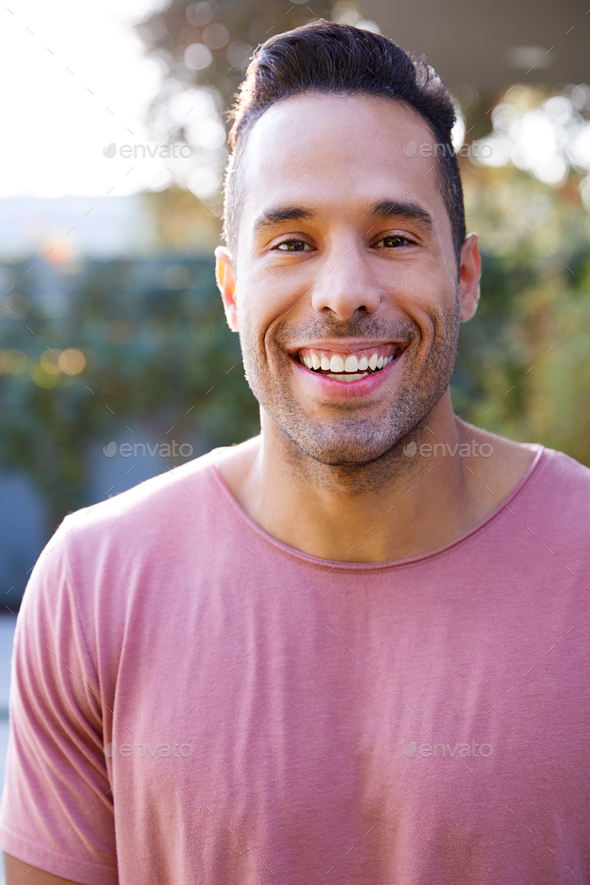 Portrait Of Smiling Hispanic Man In Garden At Home Against Flaring Sun - Stock Photo - Images