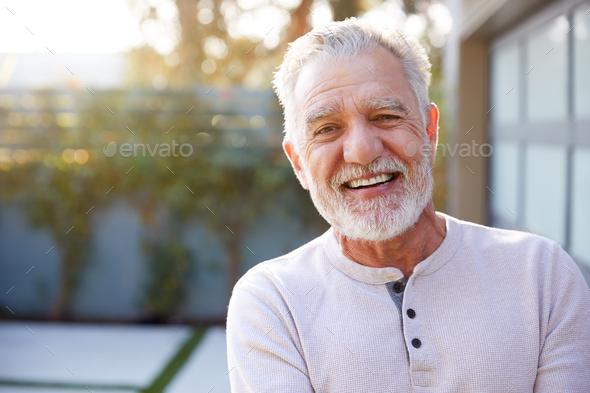 Portrait Of Smiling Retired Senior Hispanic Man In Garden At Home Against Flaring Sun - Stock Photo - Images