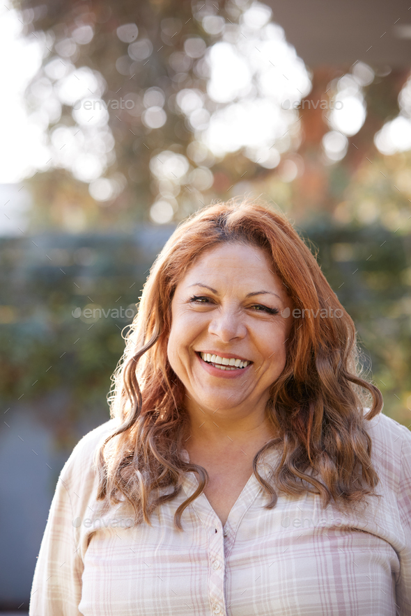 Portrait Of Smiling Senior Hispanic Woman In Garden At Home Against Flaring Sun - Stock Photo - Images