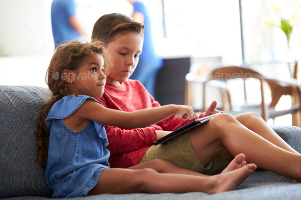 Boy And Girl Playing Video Games  On Digital Tablet During Family Gathering At Home - Stock Photo - Images