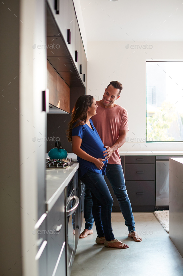 Loving Hispanic Husband With Pregnant Wife At Home In Kitchen Together - Stock Photo - Images