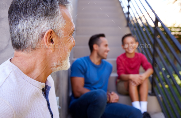 Smiling Multi-Generation Male Hispanic Family Sitting On Steps In Garden And Talking Together - Stock Photo - Images