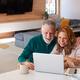Senior Hispanic Couple At Home Sitting At Table Using Laptop Together - PhotoDune Item for Sale