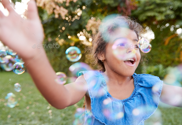 Young Hispanic Girl Chasing And Catching Bubbles In Garden - Stock Photo - Images