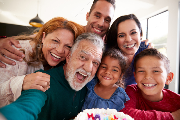 Multi-Generation Hispanic Family Taking Selfie To Celebrate Granddaughters Birthday At Home - Stock Photo - Images
