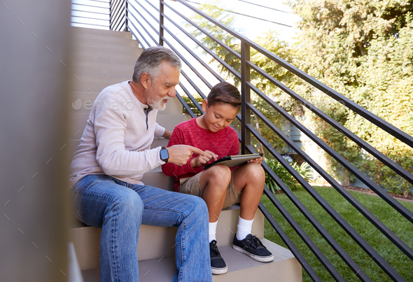 Grandfather Sitting On Steps Outdoors At Home With Grandson Using Digital Tablet - Stock Photo - Images
