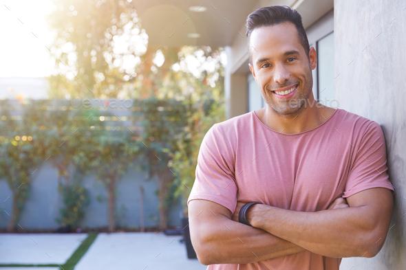 Portrait Of Smiling Hispanic Man In Garden At Home Against Flaring Sun