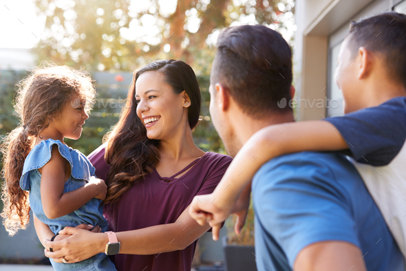 Smiling Hispanic Family With Parents Giving Children Piggyback Rides In Garden At Home - Stock Photo - Images