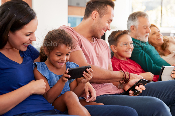 Multi-Generation Family On Sofa Watching TV And Playing With Digital Tablet And Mobile Phones - Stock Photo - Images
