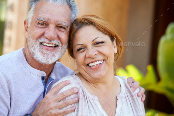 Portrait Of Smiling Senior Hispanic Couple Relaxing In Garden At Home Together - Stock Photo - Images