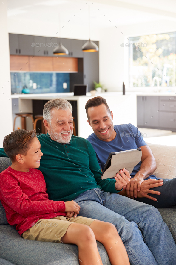 Multi-Generation Male Hispanic Family Sitting On Sofa At Home Watching Movie On Digital Tablet - Stock Photo - Images