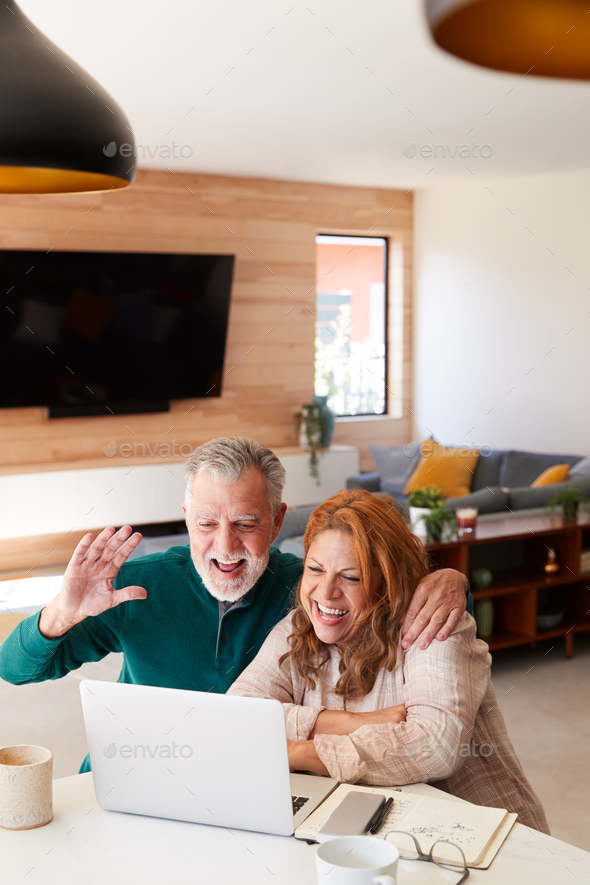 Senior Hispanic Couple At Home With Laptop Having Video Chat With Family - Stock Photo - Images