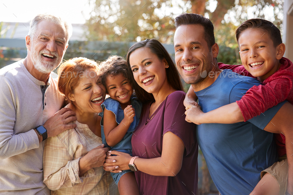 Portrait Of Multi-Generation Hispanic Family Relaxing In Garden At Home Together - Stock Photo - Images