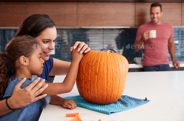 Parents With Daughter Carving Halloween Lantern From Pumpkin In Kitchen At Home - Stock Photo - Images