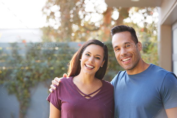 Portrait Of Smiling Hispanic Couple Relaxing In Garden At Home Together - Stock Photo - Images